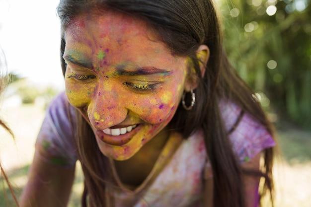 El primer de la mujer sonriente cubrió su cara con color del holi