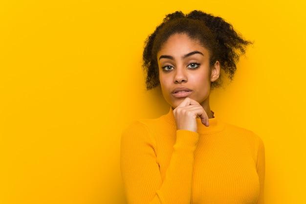 Primer negro de la mujer joven sobre una pared anaranjada