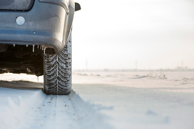 Primer del neumático de goma de las ruedas de coche en nieve profunda. concepto de transporte y seguridad.