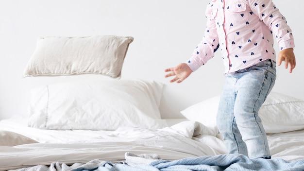Primer niño pequeño de pie en la cama