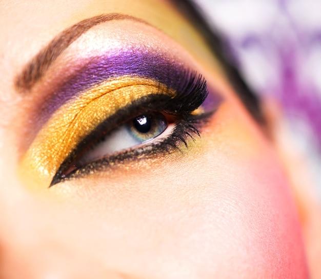 Primer ojo femenino con maquillaje brillante de moda hermosa