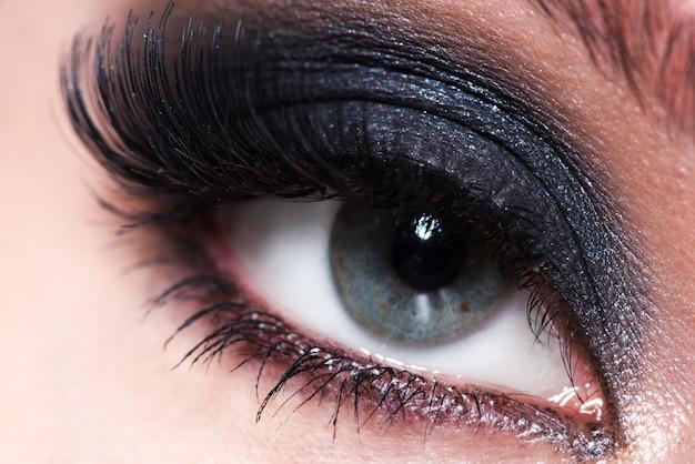 Primer ojo femenino con maquillaje de moda hermoso con largas pestañas postizas.