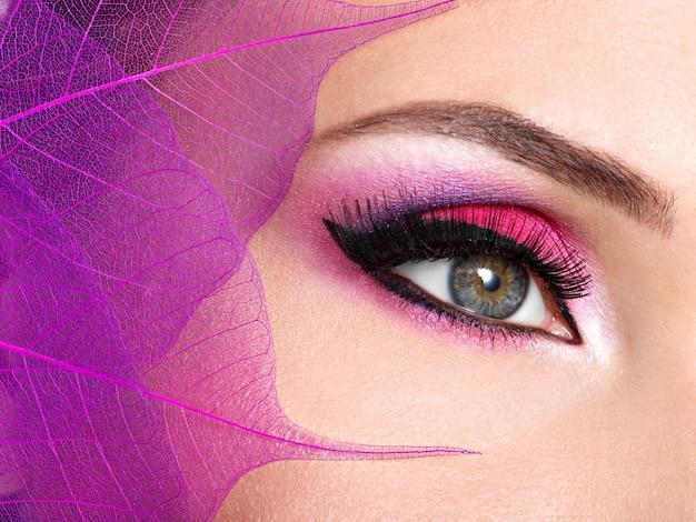 Primer ojo femenino con maquillaje rosa brillante de moda hermosa