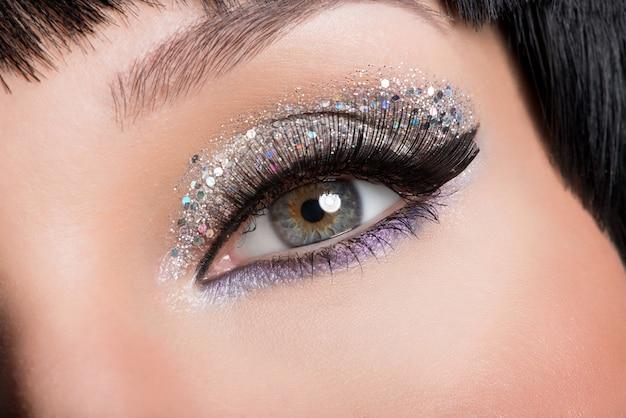 Primer ojo de mujer con maquillaje brillante de moda hermosa