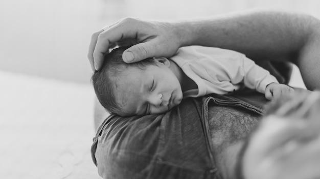 Primer padre sosteniendo sueño bebé en escala de grises
