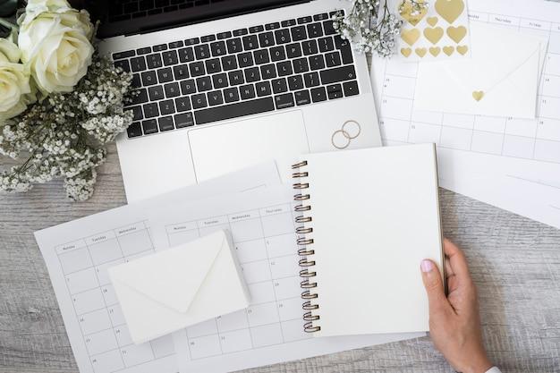 Primer de una persona que sostiene el cuaderno espiral en blanco con la computadora portátil; anillos de boda; flor; sobre y calendarios en escritorio de madera.