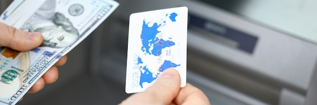 Primer de la persona que sostiene la tarjeta de crédito plástica y la pila de billetes de banco. tiro macro del cajero automático moderno para obtener salario o pensión. concepto de tecnología y finanzas