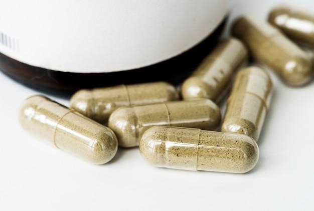 Primer de las píldoras de la cápsula aisladas en el fondo blanco
