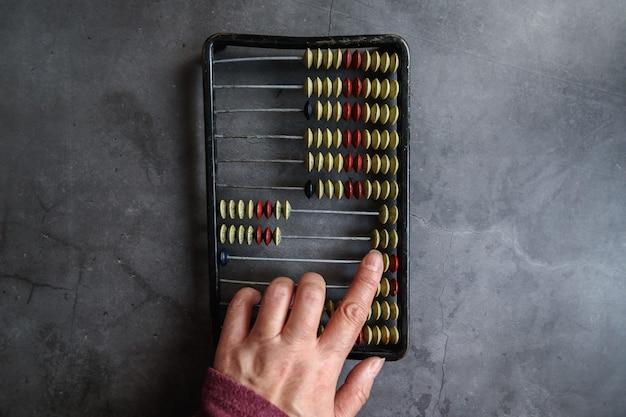 Primer plano del ábaco de la vendimia en un fondo gris. mano de mujer. el concepto de tecnologías modernas en contabilidad.