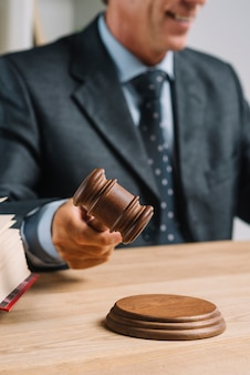 Primer plano de abogado golpeando el mazo en el bloque de sonido en el mostrador de madera