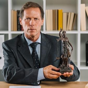 Primer plano del abogado hombre maduro confiado que muestra la estatua de la justicia