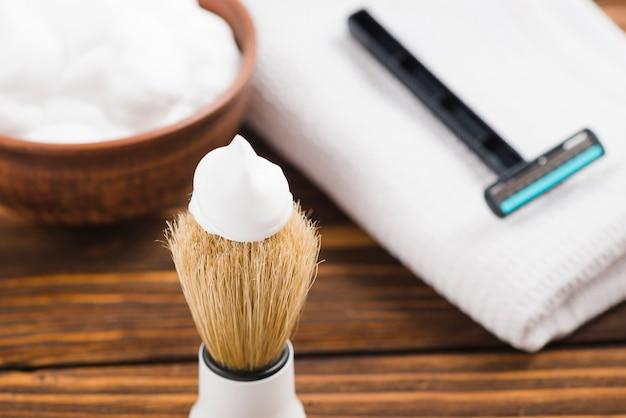 Primer plano de los accesorios de afeitado del hombre con la servilleta en la mesa de madera