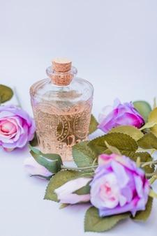 Primer plano de aceite esencial y flores artificiales.