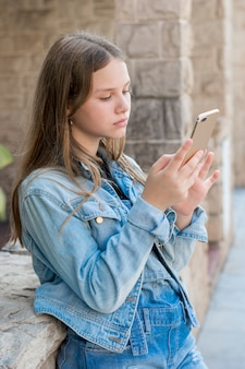 Primer plano de adolescente en denim usando teléfono inteligente al aire libre