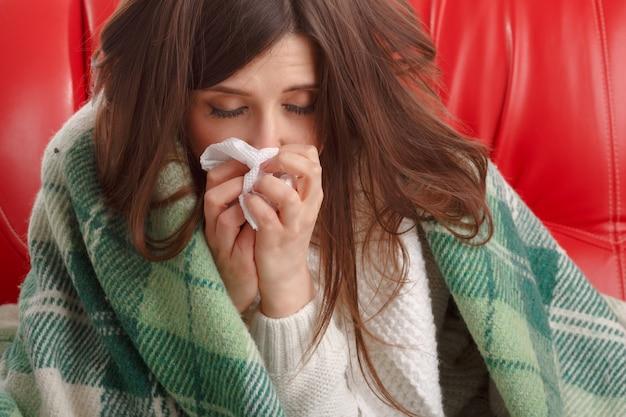 Primer plano de adolescente enferma con un pañuelo junto a su nariz