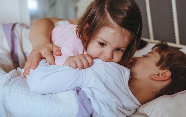 Primer plano de una adorable niña jugando con un niño acostado en la cama con su madre en una mañana relajada. concepto de tiempo de ocio familiar de fin de semana.