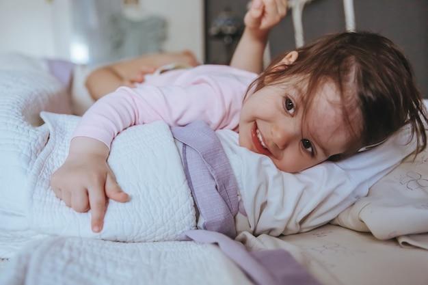 Primer plano de una adorable niña sonriente acostada en la cama en una mañana relajada. concepto de tiempo de ocio familiar de fin de semana.