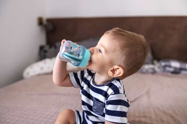 Primer plano de una adorable rubia sentada en la cama en el dormitorio y bebiendo agua de su botella.