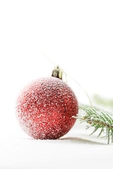Primer plano de un adorno de navidad rojo sobre la nieve.