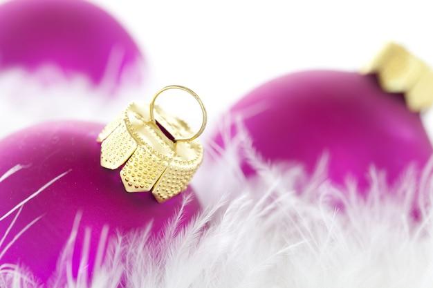 Primer plano de adornos navideños de color púrpura y plumas bajo las luces con un fondo borroso