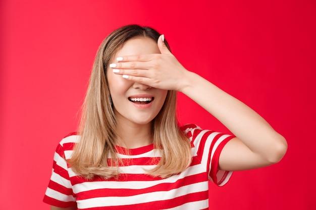 Primer plano afortunado linda mujer rubia asiática sonriendo ampliamente contar diez prometer no asomarse cubrir los ojos con la palma de la mano ...