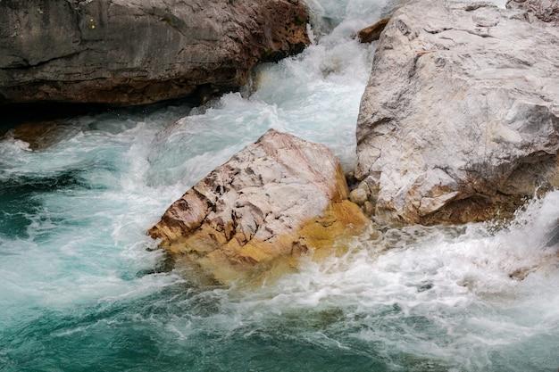 Primer plano del agua golpeando las rocas en el parque nacional del valle de valbona en albania