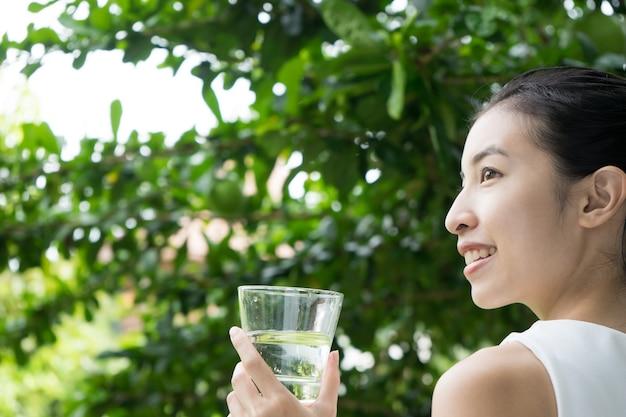 Primer plano de agua potable de niña bonita de vidrio
