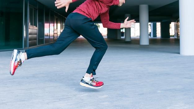 Primer plano de ajuste y saludable hombre corriendo al aire libre