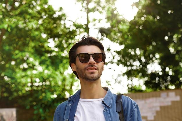 Primer plano al aire libre del encantador joven con barba posando sobre el parque verde en un día soleado, con gafas de sol y ropa casual, estando de buen humor