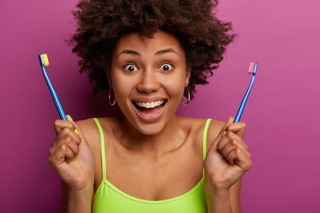 Primer plano de alegre mujer afroamericana tiene dos cepillos de dientes
