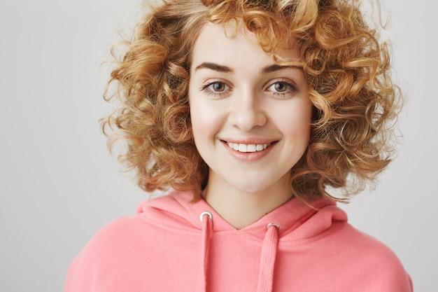 Primer plano de la alegre niña de pelo rizado de ensueño sonriendo