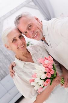 Primer plano de una alegre pareja de ancianos con un hermoso ramo de flores de tulipán