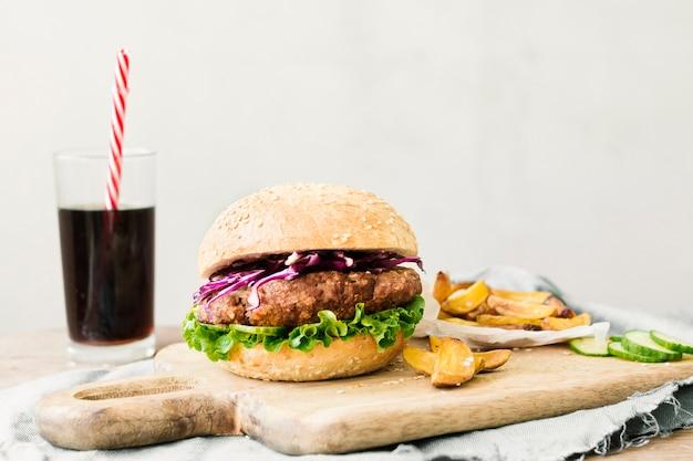 Primer plano de alto ángulo de hamburguesa y papas fritas en tablero de madera