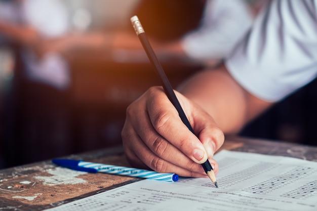 Primer plano del alumno sosteniendo el lápiz y escribiendo el examen final