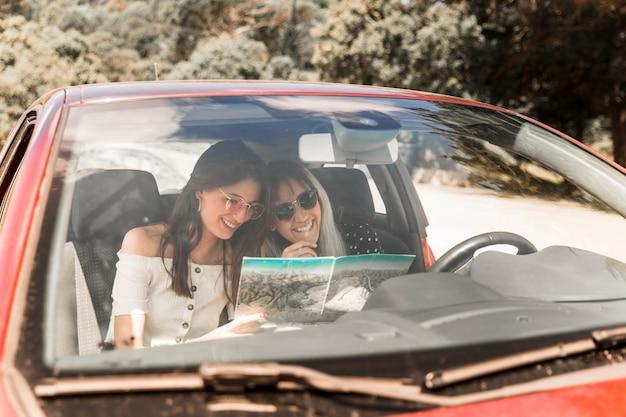 Primer plano de amigas sentadas en el coche mirando el mapa