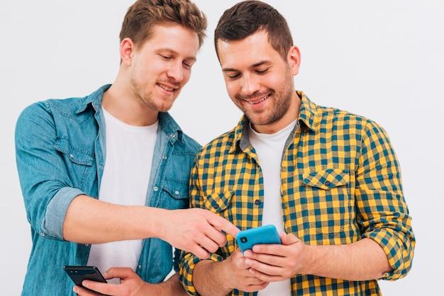 Primer plano de amigo masculino que muestra algo en el teléfono móvil