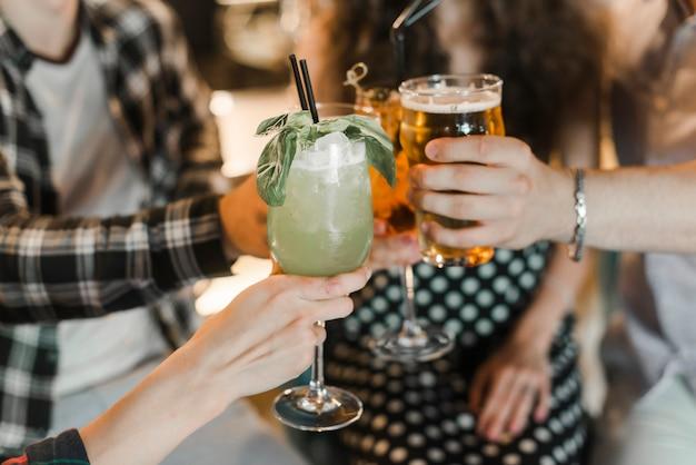 Primer plano de amigos brindando diferentes tipos de bebidas
