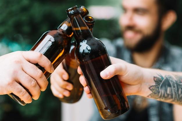 Primer plano de amigos están tintineando las botellas de cerveza al aire libre
