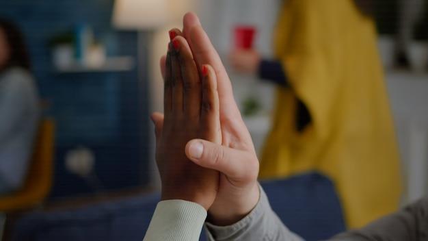 Primer plano de amigos multiétnicos dando cinco durante la fiesta de celebración mientras está sentado en el sofá hasta tarde ...