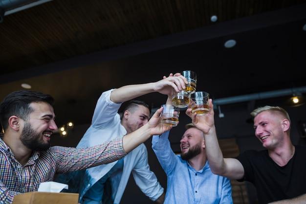 Primer plano de amigos sonrientes tostado vasos de bebidas en el desnudo