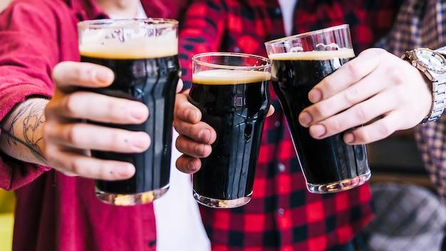 Primer plano de amigos tintineando los vasos de cerveza