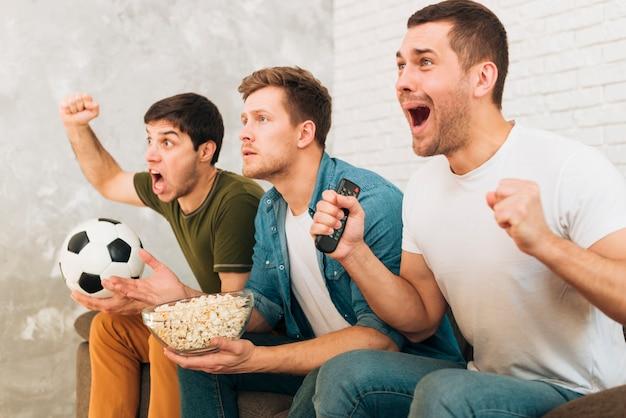 Primer plano de amigos viendo un partido de fútbol gritando y gritando