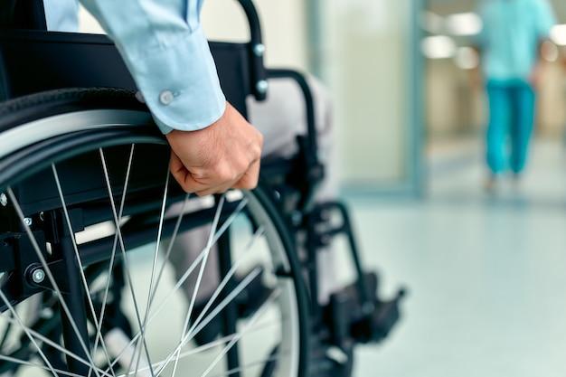 Primer plano de anciano discapacitado sentado en silla de ruedas siendo atendido en el hospital, abuelo maduro discapacitado en silla de ruedas, concepto de discapacidad de ancianos.