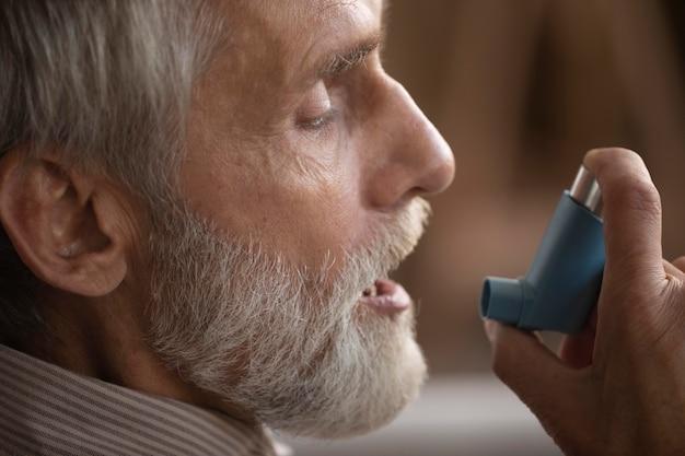 Primer plano anciano sosteniendo inhalador para el asma