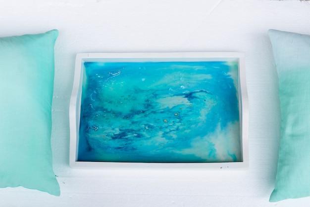 Primer plano de ángulo alto de una bandeja blanca con arte de resina epoxi con tintas de alcohol azul