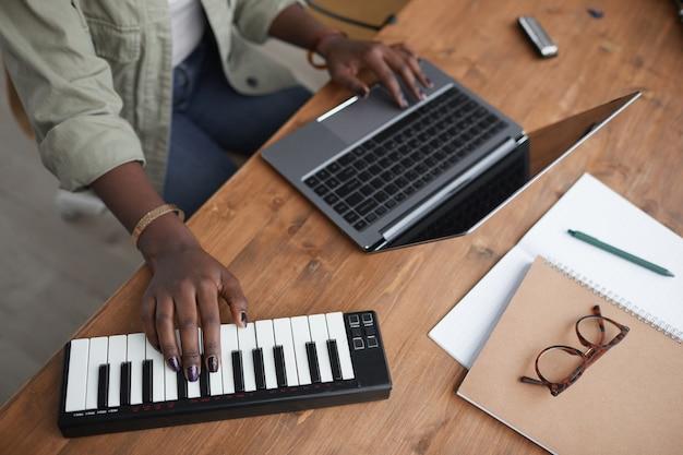 Primer plano de ángulo alto irreconocible mujer afroamericana componer música en el estudio de grabación en casa, espacio de copia