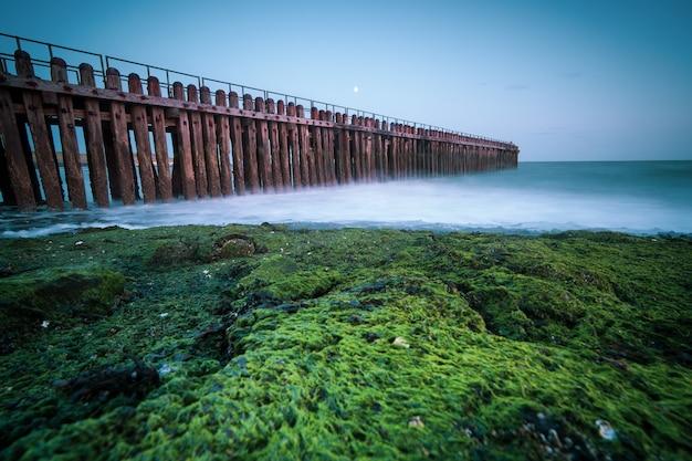 Primer plano de ángulo alto de una valla de madera en la orilla del mar que conduce al mar