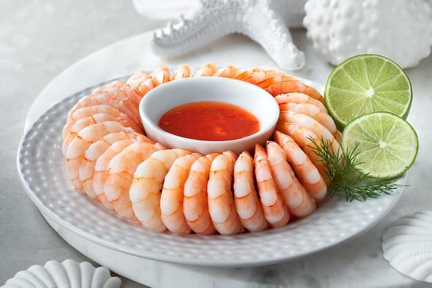 Primer plano de anillo de camarones con salsa de chile dulce con eneldo y lima
