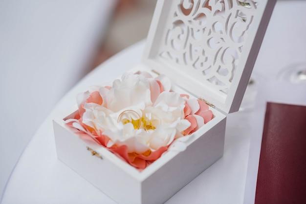 Primer plano de anillos de boda en una hermosa caja, durante la reunión de la novia. accesorios.