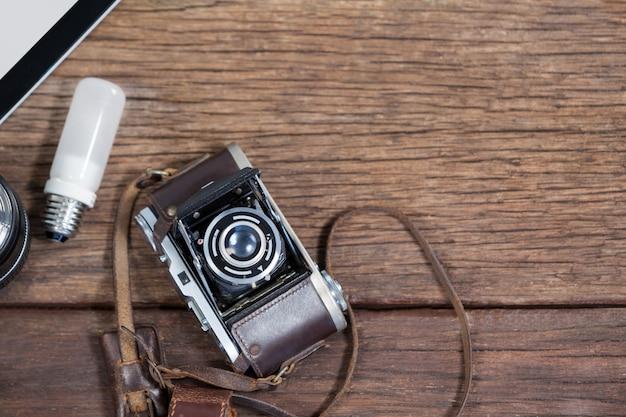 Primer plano de la antigua cámara, lente, bombilla en la mesa